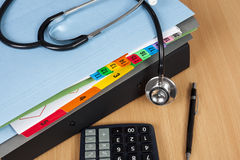 Stethoscope laying on a pile of hospital patient records royalty free stock image