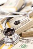 Stethoscope Laying on Stacks of Money Stock Photos