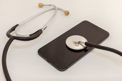 Stethoscope is leaning against the screen of a black smartphone. royalty free stock photography