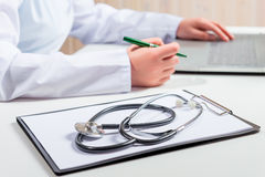 Stethoscope lies on a folder on the table and the doctor Royalty Free Stock Image