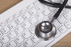 Stethoscope lying on a computer keyboard. In a concept of troubleshooting and repair or of online medical assistance Stock Images