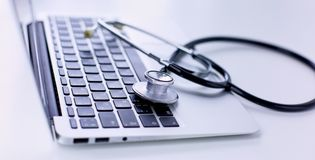 Stethoscope lying on a laptop keyboard in a concept of online medicine or troubleshooting the computer viewed low angle. With copy space stock photo