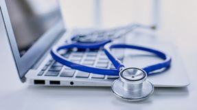 Stethoscope lying on a laptop keyboard in a concept of online medicine or troubleshooting the computer viewed low angle. With copy space stock photography