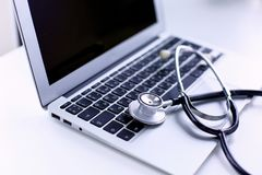 Stethoscope lying on a laptop keyboard in a concept of online medicine or troubleshooting the computer viewed low angle. With copy space stock images