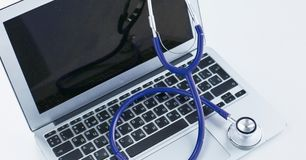 Stethoscope lying on a laptop keyboard in a concept of online medicine or troubleshooting the computer viewed low angle. With copy space stock photos