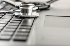 Stethoscope lying on a laptop keyboard Stock Photography