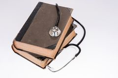 Stethoscope lying on a old reference books. Medical literature concept stock image