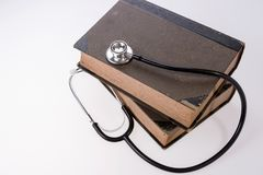 Stethoscope lying on a old reference books. Medical literature concept stock photography