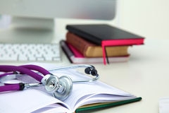 Stethoscope lying on a table on an open book.  stock photography