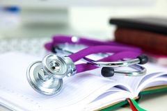 Stethoscope lying on a table on an open book Royalty Free Stock Photo