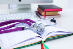 Stethoscope lying on a table on an open book Stock Photos