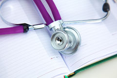 Stethoscope lying on a table on an open book Royalty Free Stock Photos