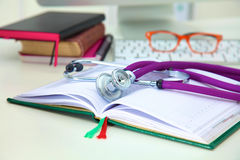 Stethoscope lying on a table  an open book Royalty Free Stock Photo