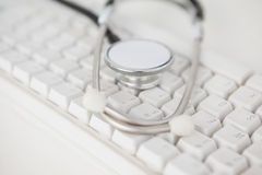 Stethoscope lying on white keyboard Royalty Free Stock Image