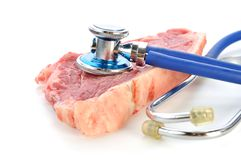 Stethoscope on the meat. Stethoscope on the unhealthy fat meat Stock Image