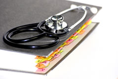 Stethoscope on medical folder. Stethoscope on top of a thick medical folder, isolated on a white background Stock Photos