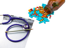 A stethoscope ,medical history folder clipboard and colorful tablets medicine in black bottle on white Stock Images