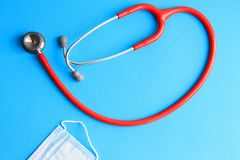 Stethoscope and medical mask on a blue background stock image