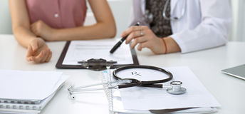 Stethoscope, medical prescription form are lying against the background of a doctor and patient discussing health exam Stock Images