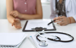 Stethoscope, medical prescription form are lying against the background of a doctor and patient discussing health exam Royalty Free Stock Photo