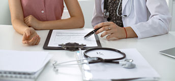 Stethoscope, medical prescription form are lying against the background of a doctor and patient discussing health exam