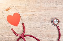 Stethoscope medical with red heart. Stethoscope medical with red heart on wooden background with free space for your text or message stock photography
