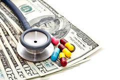 Stethoscope, medicine capsules and banknotes Stock Photo