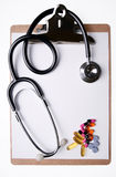 Stethoscope and medicine on clipboard Royalty Free Stock Images