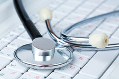 Stethoscope on a modern keyboard Stock Photos
