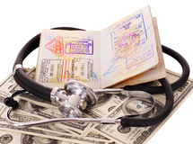 Stethoscope, money and passport. Royalty Free Stock Image