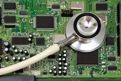 Stethoscope on motherboard. A stethoscope on a computer circuit board. Possible concept uses: computer health,  technology in health care, diagnosing/ Stock Photo