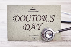 Stethoscope near Doctor`s Day card. Greeting paper and wooden background. Stressful and honorable profession Stock Photo