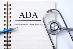 Stethoscope on notebook and pencil with ADA Americans with Disa. Bilities Act words as medical concept royalty free stock images