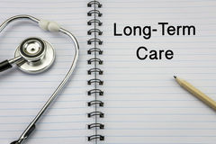 Stethoscope on notebook and pencil with Long Term Care Royalty Free Stock Photo