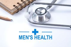 Stethoscope, notebook and pencil with men`s health words. Health