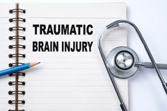 Stethoscope on notebook and pencil with Traumatic Brain Injury. Words as medical concept royalty free stock photography