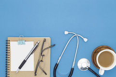 Stethoscope with notebook ,pencil, white paper ,coffee cup,glass Royalty Free Stock Images