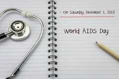 Stethoscope on notebook and pencil with world aids day words as stock images