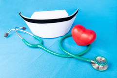 Stethoscope and nurse hat. Stethoscope, nurse hat and heart red ceramic on blue fabric royalty free stock images