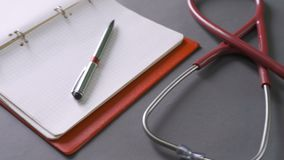 Stethoscope in the office of doctors. Top view of doctor`s desk table, blank paper on clipboard with pen stock video