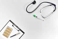 Stethoscope in the office of doctors.Top view of doctor`s desk table, blank paper on clipboard with pen. Copy space royalty free stock photography