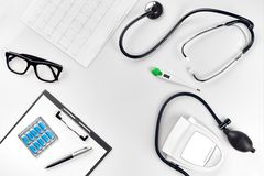 Stethoscope in the office of doctors.Top view of doctor`s desk table, blank paper on clipboard with pen. Copy space stock images