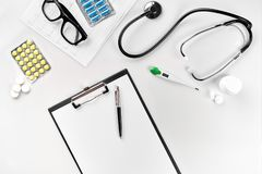 Stethoscope in the office of doctors.Top view of doctor`s desk table, blank paper on clipboard with pen. Copy space