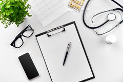 Stethoscope in the office of doctors. Top view of doctor`s desk table, blank paper on clipboard with pen. Copy space. Designer`s blank. Still life. Flat lay stock image
