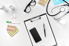 Stethoscope in the office of doctors.Top view of doctor`s desk table, blank paper on clipboard with pen. Copy space royalty free stock photos