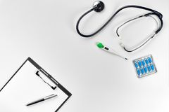 Stethoscope in the office of doctors.Top view of doctor`s desk table, blank paper on clipboard with pen. Copy space stock photo