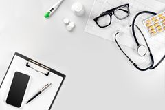 Stethoscope in the office of doctors.Top view of doctor`s desk table, blank paper on clipboard with pen. Copy space. Designer`s blank. Still life. Flat lay Stock Photo