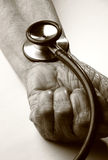 Stethoscope on old hand Stock Photography