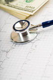 Stethoscope over ecg graph and 100 dollar Stock Photos