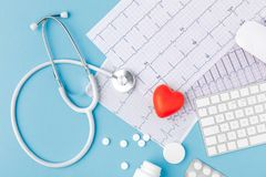 Stethoscope, paper with cardiogram, scattered pills, red heart and keyboard Stock Photography